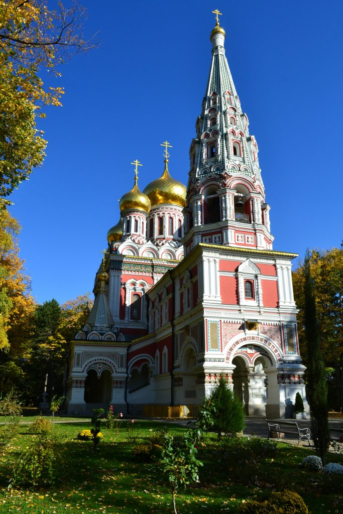 Large Russian Orthodox church with soft pink highlights and golden onion domes situated in a lush garden with grass and leafy trees with their fall colors